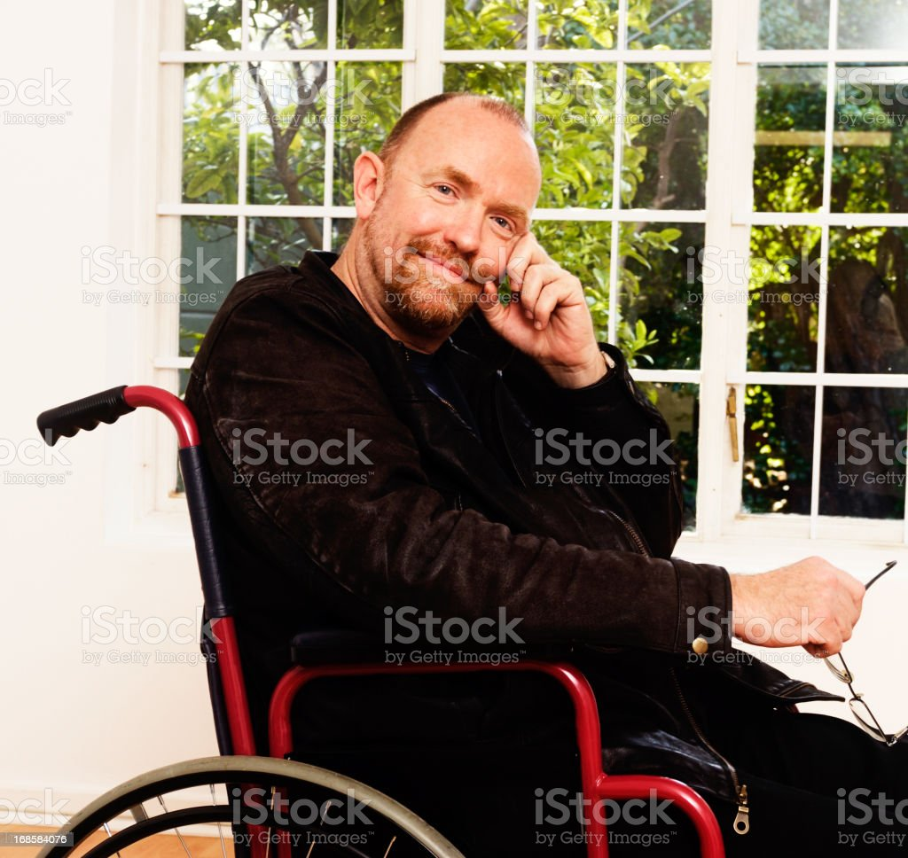 Gently smiling, serene man in wheelchair, apparently content with life stock photo