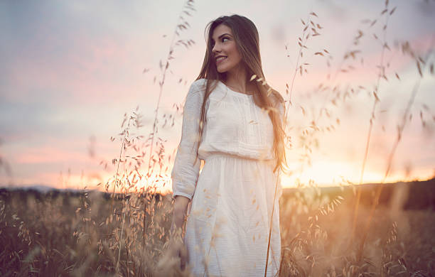 Genuine Glow Portrait of a beautiful caucasian woman at sunset. sun shining through dresses stock pictures, royalty-free photos & images
