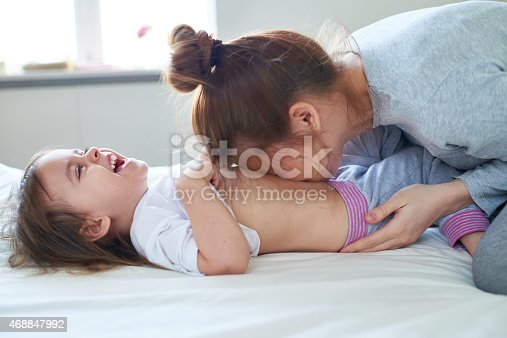 Affectionate mother kissing her happy daughter on belly