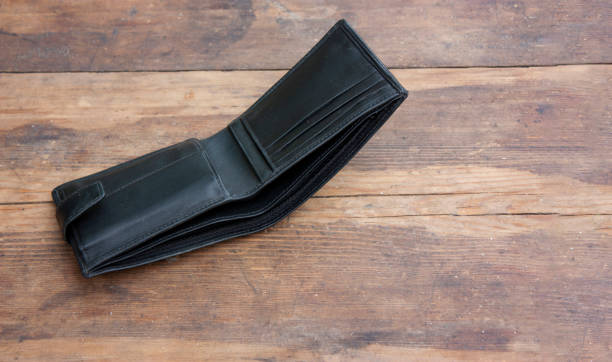 A genuine leather wallet is lying empty on an old wooden table. Concept economic crisis, poverty, unemployment. Copyspace stock photo