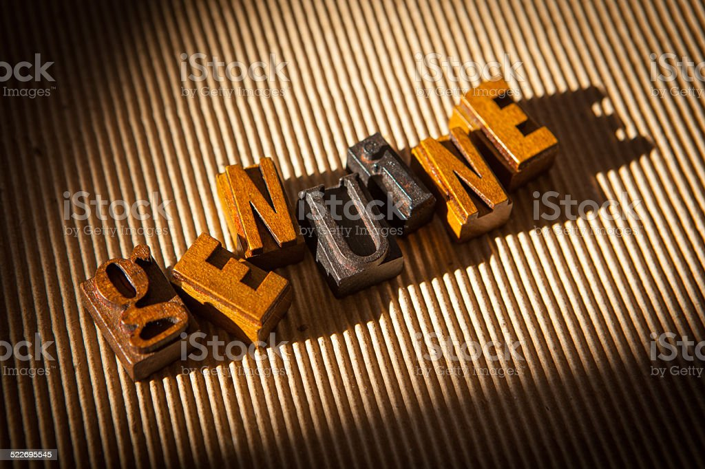 Genuine spelled out in wooden block letterpress letters stock photo