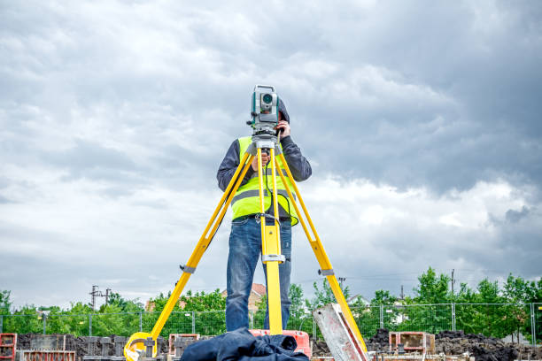 Geodesist is working with total station on a building site. Civil engineer with theodolite equipment during surveyor work stock photo