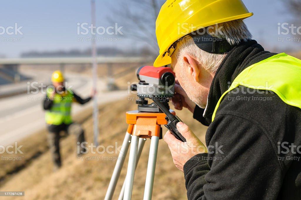 Geodesist measure land with tacheometer highway stock photo