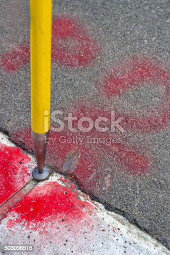 istock Geodetic survey mark set in asphalt 503096515