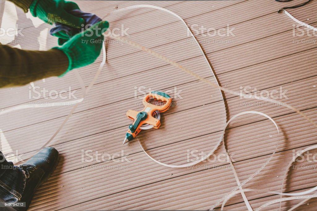 geodetic tape measure lies on floor. Hands wipe tape stock photo