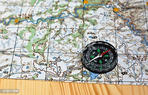 97623256istockphoto Geographical map and a compass. 479377936