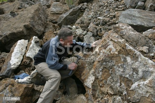 geologist scientist looking at rock outcrop with his hammer