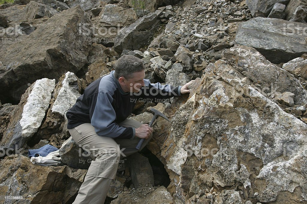Geologist scientist man looking at rock in quarry stock photo