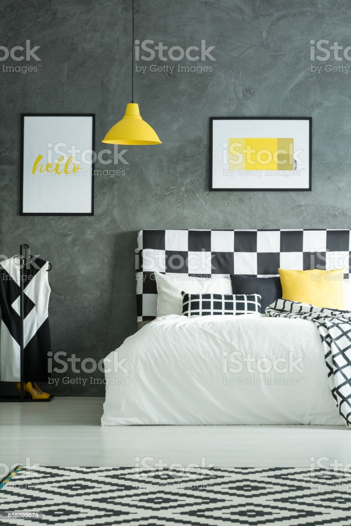 Black and white geometric carpet in dark bedroom with yellow lamp...