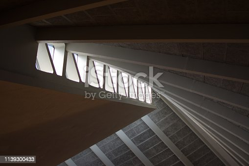 Graphic geometric ceiling constructed from a series of concrete rafters. Juxtaposition of curves and straight lines. Light flooding in through triangle shaped roof lights.