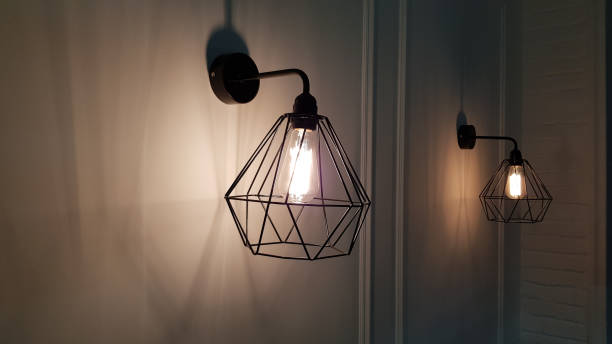Geometric pendant light closeup on blurry background. Diamond shape wire lampshade with light bulb inside. Sconce lamps hanging on wall background with shadows and copy space. Interior lighting. stock photo