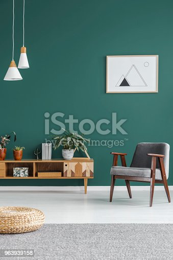 Simple geometric poster hanging on the wall in green living room interior with grey armchair, wooden cupboard and fresh plants