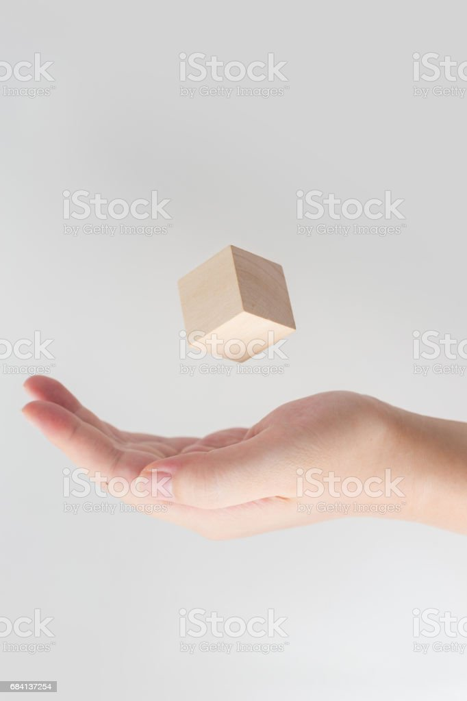 geometric real wooden cube float on hand foto stock royalty-free