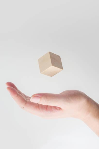 geometrische echte holzwürfel schweben auf seite - einfache holzprojekte stock-fotos und bilder