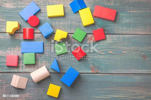 istock Geometric shapes for kids logical thinking. Colorful wooden blocks on green wooden background. Children's building blocks. 861148488