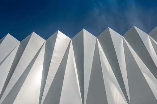 Abstract background with a white triangular pattern on a clear sky background. Siding on the wall of a public parking lot to provide shade and passage of the breeze.