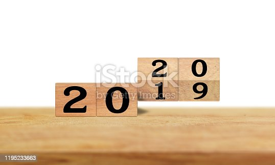 istock Geometric wooden cube change from past last year 2019 to new year 2020 on wood table and white background. 1195233663