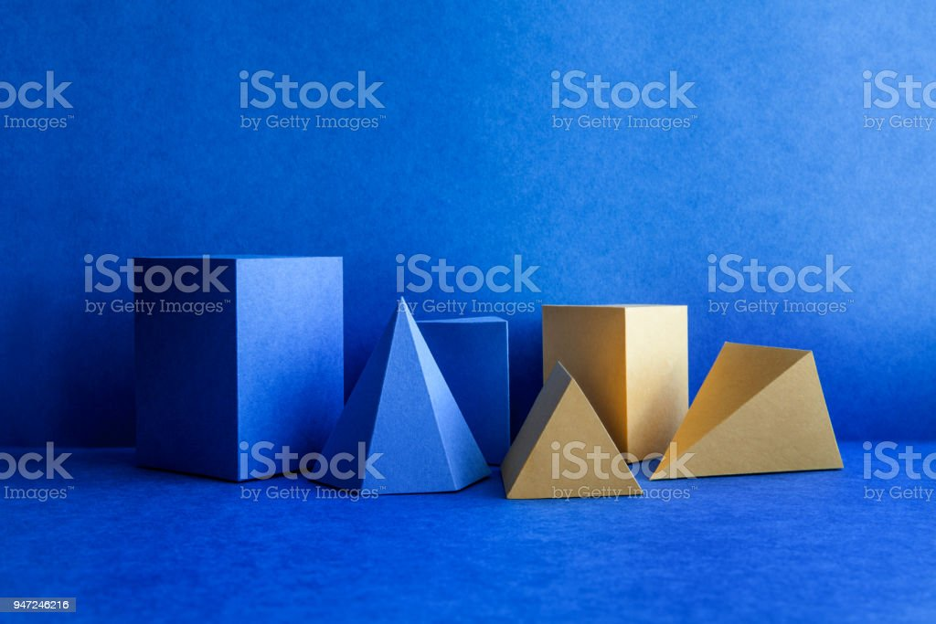Geometrical figures still life composition. Three-dimensional blue yellow prism pyramid tetrahedron rectangular cube objects on blue background. Platonic solids figures, simplicity concept photography stock photo