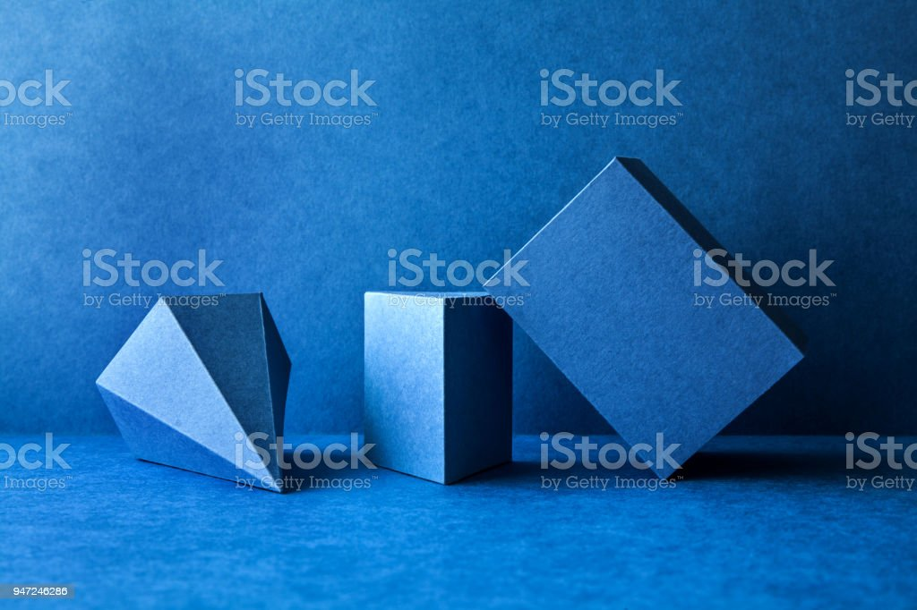 Geometrical figures still life composition. Three-dimensional prism pyramid tetrahedron rectangular cube objects on blue background. Platonic solids figures, simplicity concept photography stock photo