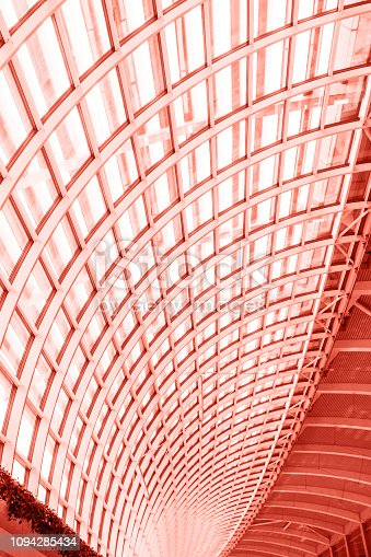 istock Geometry glass roof pattern structure in building toned in coral color. 1094285434
