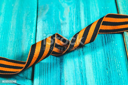 istock George Ribbon in hands. Symbol of May 9 - George Ribbon striped, orange and black . Memory Soviet victory over Germany in the Great Patriotic War in 1945. 803503248