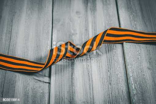 istock George Ribbon in hands. Symbol of May 9 - George Ribbon striped, orange and black . Memory Soviet victory over Germany in the Great Patriotic War in 1945. 803519914