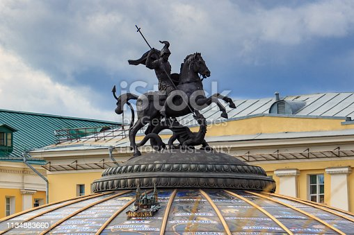 Moscow, Russia - September 30, 2018: George the Victorious closeup on dome of World Clock Fountain on Manezhnaya Square in Moscow against dramatic sky at cloudy autumn day