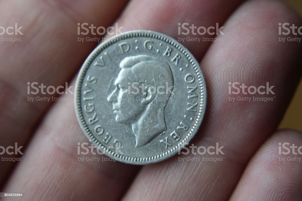 George VI shilling on fingers stock photo