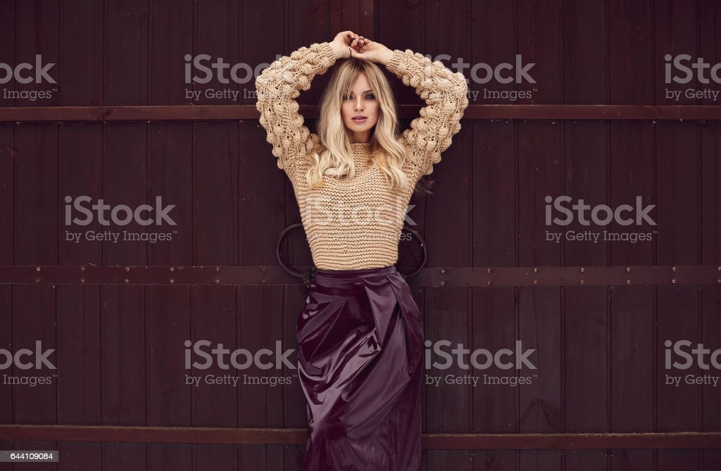 Georgeous elegant blonde in bright dress on wooden background stock photo