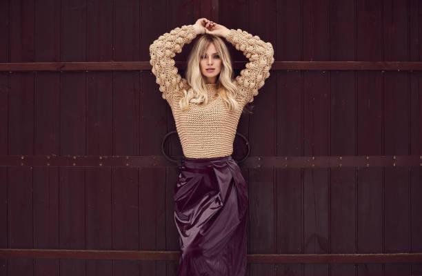 georgeous rubia elegante vestido brillante sobre fondo de madera - moda de invierno fotografías e imágenes de stock