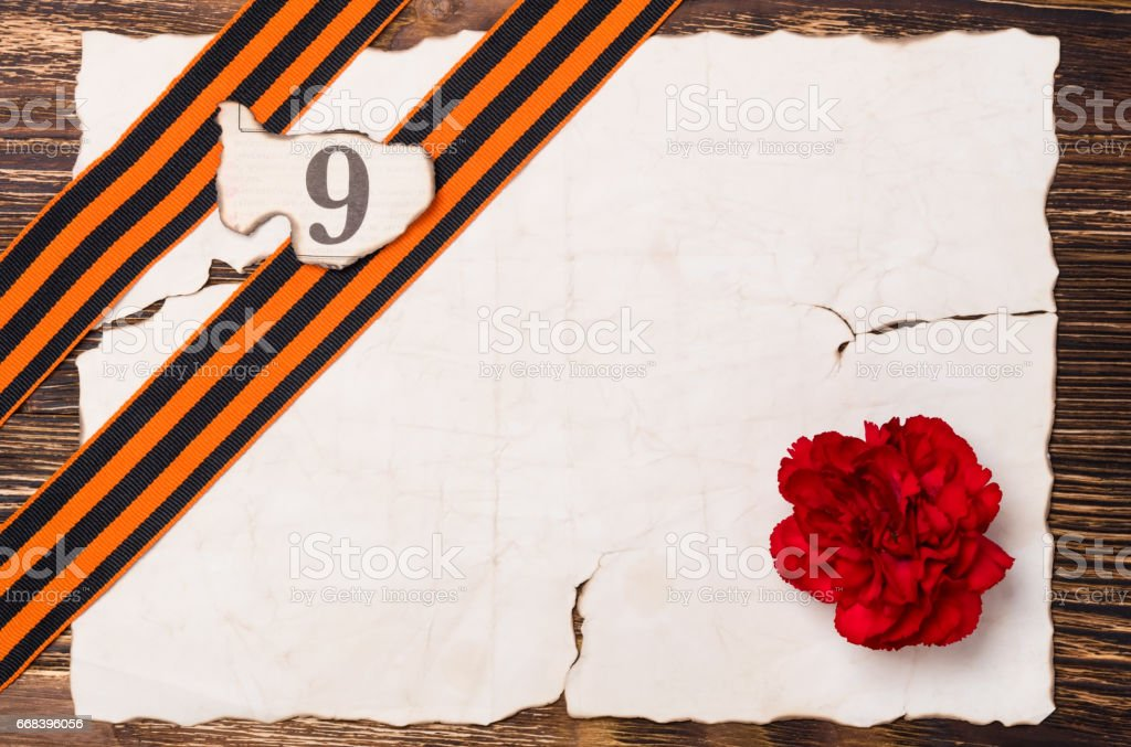 George's tape is on an old paper with a red carnation stock photo