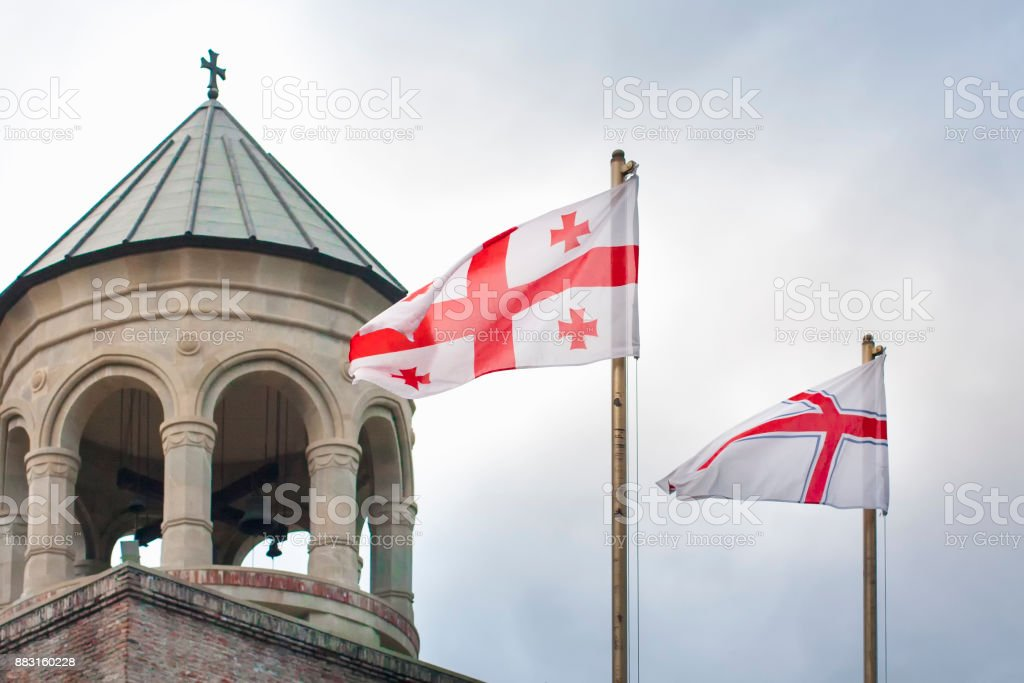 Georgia flags with ancient georgian church and sky in background. stock photo