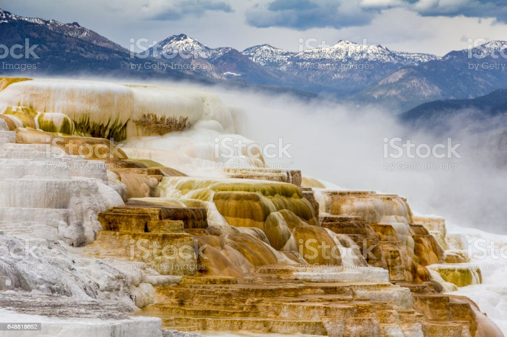 Geothermal flow of hot, carbonate rich water, forms cascading, dark orange travertine terraces, with mountains in the background, at Mammoth Hot Springs in Yellowstone National Park, Wyoming. stock photo