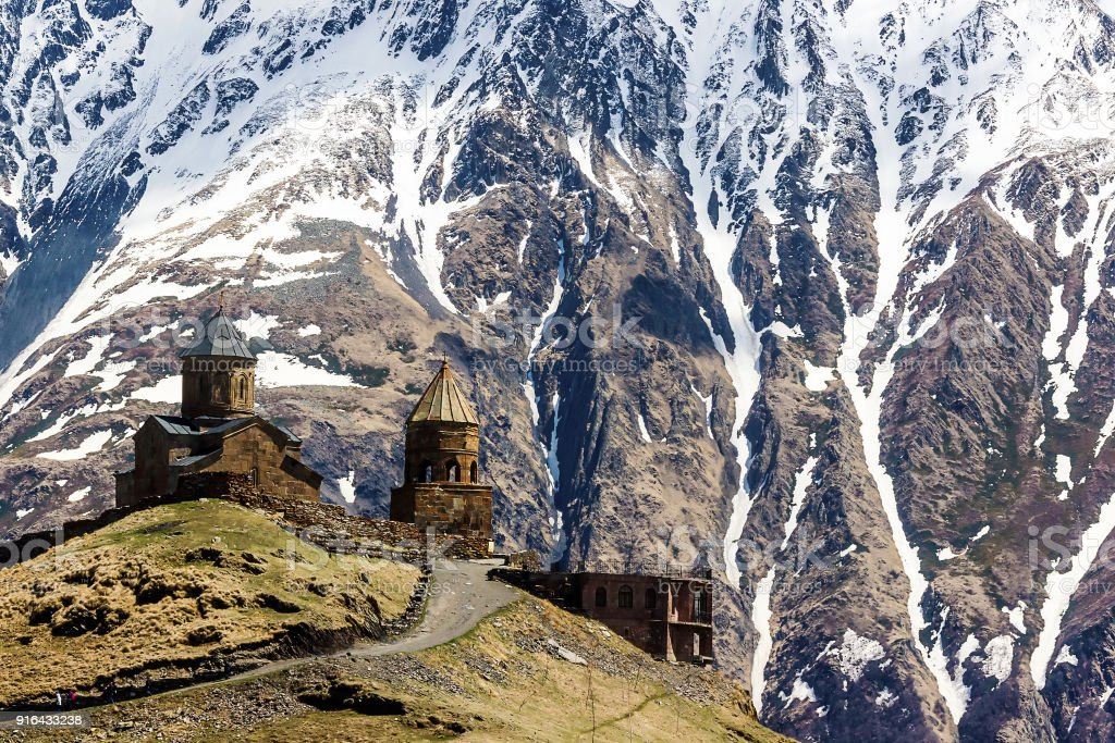 Gergeti trinity church (Tsminda Sameba), mountain Kazbek, Georgia  on the background of snow-covered Caucasus mountains stock photo