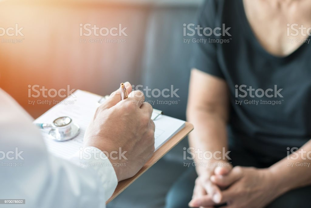 Geriatric doctor (geriatrician) consulting and diagnostic examining elderly senior adult patient (older person) on aging and mental health care in medical clinic office or hospital examination room stock photo
