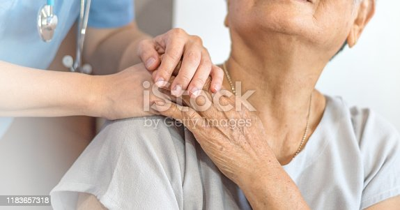 istock Geriatric doctor or geriatrician concept. Doctor physician hand on happy elderly senior patient to comfort in hospital examination room or hospice nursing home or wellbeing county. 1183657318