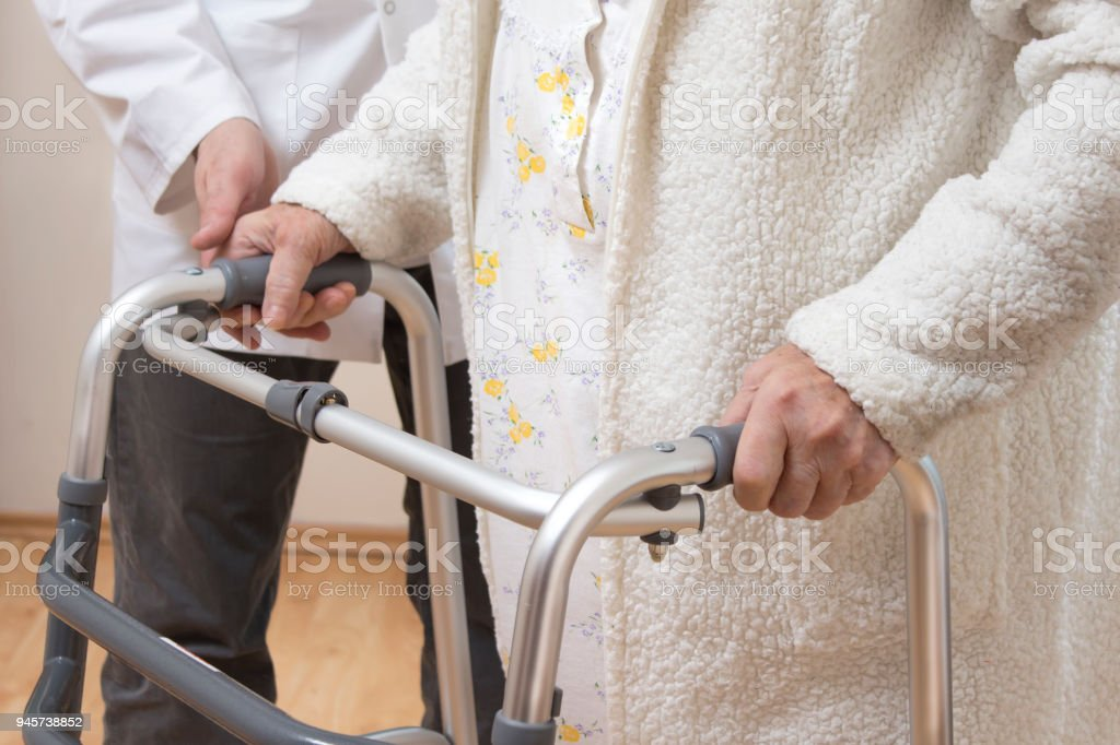 A geriatric doctor teaches to walk an old woman using a rehabilitation walker. The nurse helps the old woman to walk with rehabilitation walker stock photo
