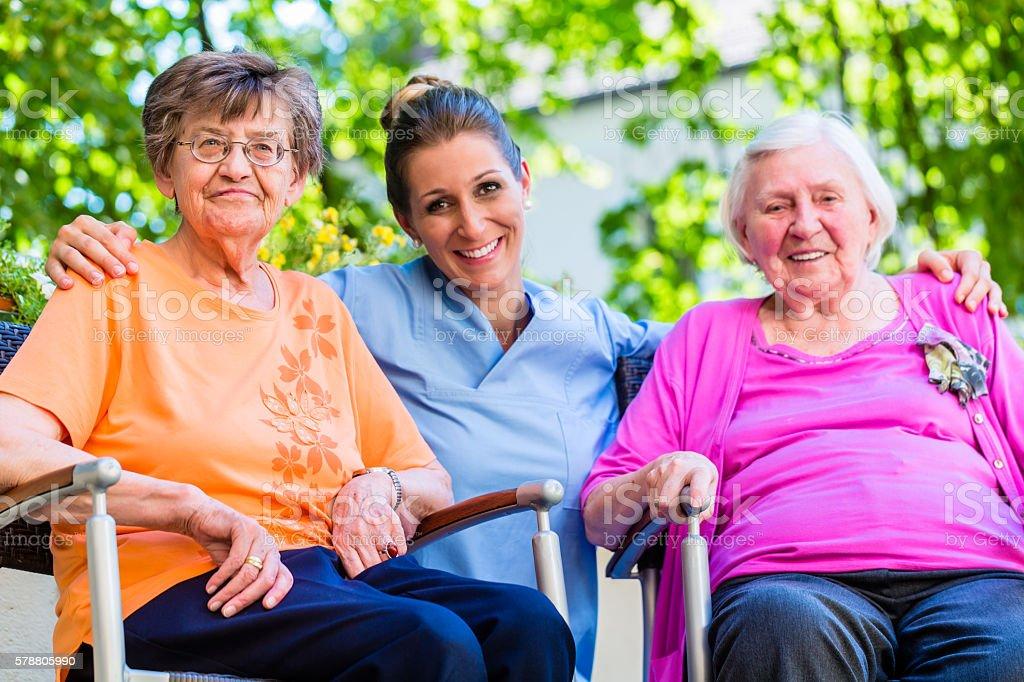 Geriatric nurse having chat with senior women - サービスのロイヤリティフリーストックフォト