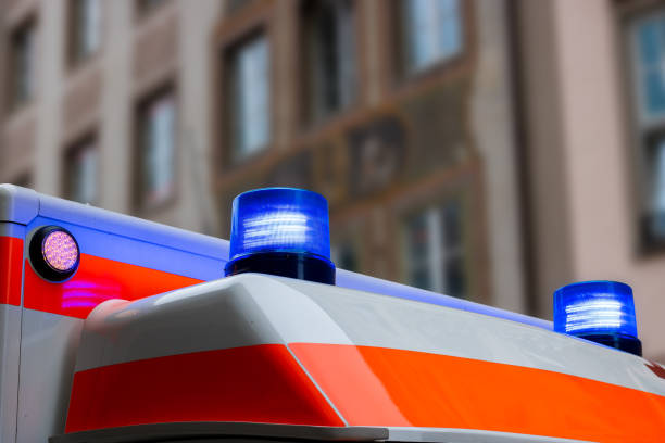 A german ambulance car with flashing blue lights in an urban area A german ambulance car with flashing blue lights in an urban area ambulance staff stock pictures, royalty-free photos & images