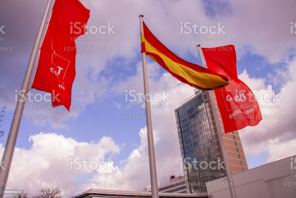 German and Cebit flags against cloud sky at CeBIT trade show in Hannover, Germany on March 2, 2010. stock photo