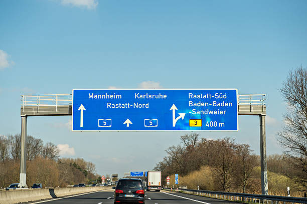 German autobahn blue street sign cars Munchen, Germany - March 26, 2016: Bundesautobahn or Federal Motorway highway street signs to Mannheim, Karsruhe, Rastatt-Nord, Baden-Baden and Sandweier singen stock pictures, royalty-free photos & images