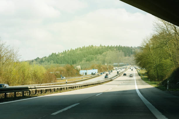 German Autobahn with cars on a sunny day Stuttgart, Germany - March 26, 2016: Sunny day over German highway - Bundesautobahn or Federal Motorway highway with busy traffic on a spring day with beautiful green fields and blue clouds singen stock pictures, royalty-free photos & images