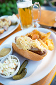 German Bratwurst on a roll with sauerkraut and a beer