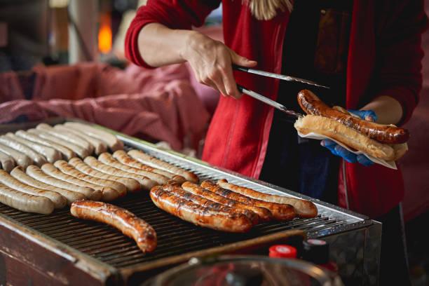 deutsche bratwurst wurst zubereitet auf dem grill in einer örtlichen bauernmarkt. - bratwurst mit sauerkraut stock-fotos und bilder