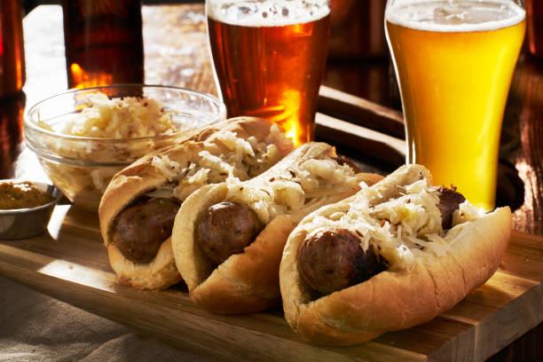 deutsche bratwürste und sauerkraut mit bier - bratwurst mit sauerkraut stock-fotos und bilder
