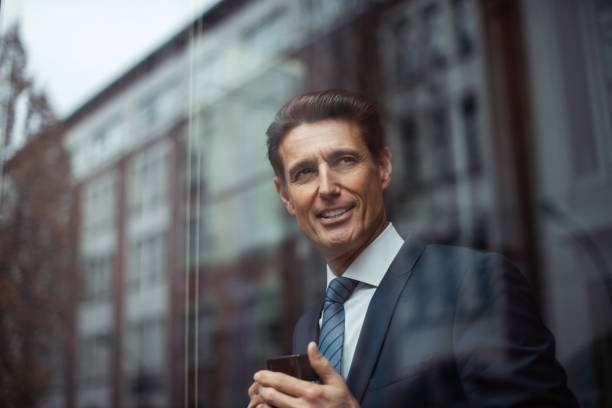 German businessman - looking through window Formally dressed 55-year-old businessman is standing in the bright office and looking through the window while holding a hot drink mug. georgijevic frankfurt stock pictures, royalty-free photos & images
