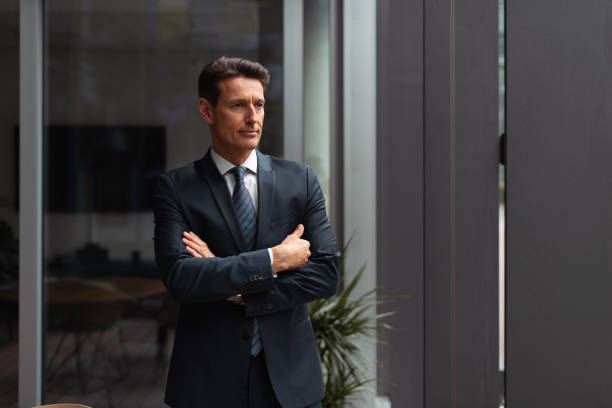 German businessman - looking through window Formally dressed 55-year-old businessman is standing in the bright office and looking through the window. georgijevic frankfurt stock pictures, royalty-free photos & images