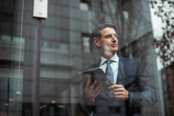 German businessman Formally dressed 55-year-old businessman is holding a digital tablet and looking through the window of the bright office. georgijevic frankfurt stock pictures, royalty-free photos & images