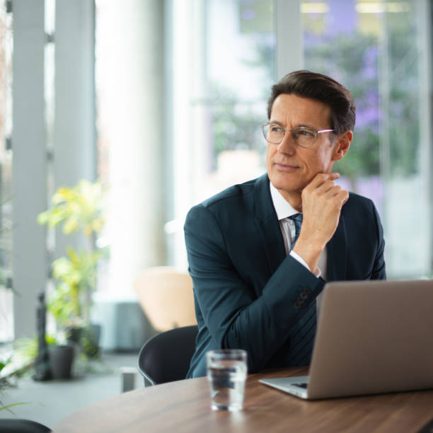 German businessman Formally dressed 55-year-old businessman is working on a laptop in the office. georgijevic frankfurt stock pictures, royalty-free photos & images