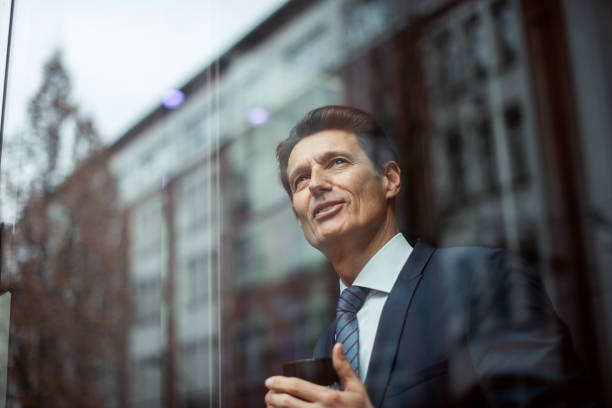 German businessman Formally dressed 55-year-old businessman is standing in the bright office and using smartphone. georgijevic frankfurt stock pictures, royalty-free photos & images